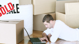 Man using the laptop during his home move Footage