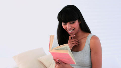 Attractive woman reading a book on her bed Footage