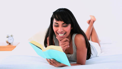 Attractive woman reading a book lying on her bed Footage