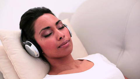 Attractive woman lying on couch listening to music Footage