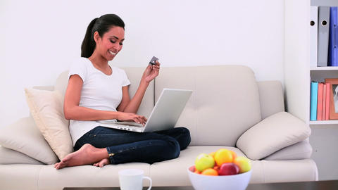 Attractive woman sitting on couch using her laptop Footage
