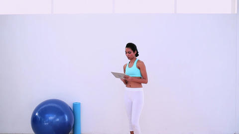 Fit woman using her digital tablet standing Footage