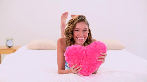 Cheerful woman holding a heartshaped pillow relaxi Footage