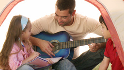 Two kids with their dad playing the guitar Footage