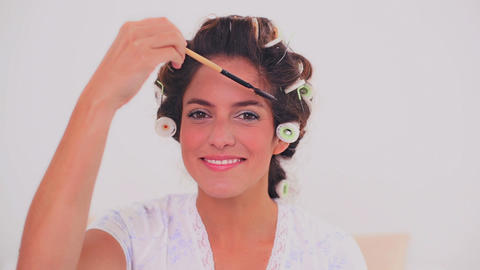 Smiling woman in hair curlers brushing her eyebrow Footage