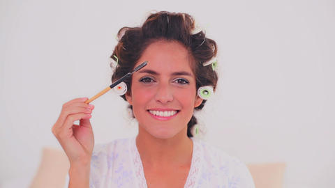 Smiling woman in hair curlers brushing her eyebrow Stock Video Footage