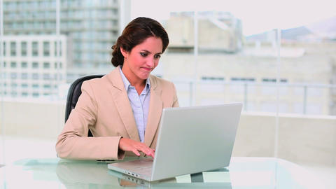 Concentrated attractive businesswoman using a lapt Footage