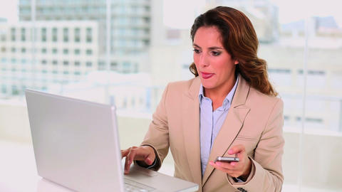 Seductive brunette businesswoman typing on laptop  Footage
