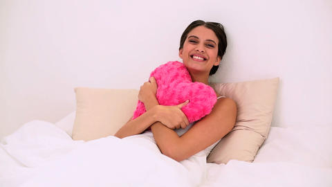 Happy beautiful woman lying on a bed cuddling a he Footage