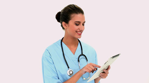 Thoughtful beautiful nurse using a tablet pc Footage