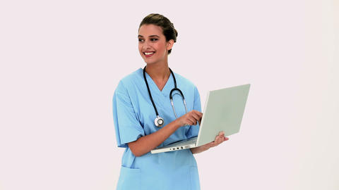 Amused beautiful nurse using a laptop Footage