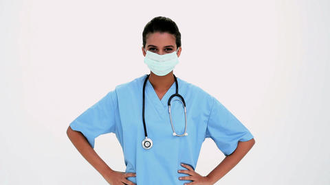 Smiling beautiful nurse putting a surgical mask Footage