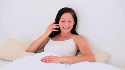 Attractive brunette speaking on the phone in bed Footage