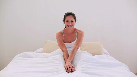 Attractive brunette smiling at bedtime in bed Footage