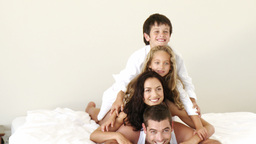 Family lying on bed smiling having fun Footage