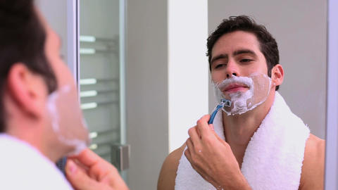 Handsome man looking at mirror and shaving Footage