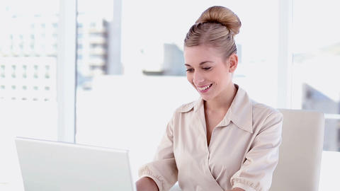 Smiling blonde businesswoman using laptop Footage