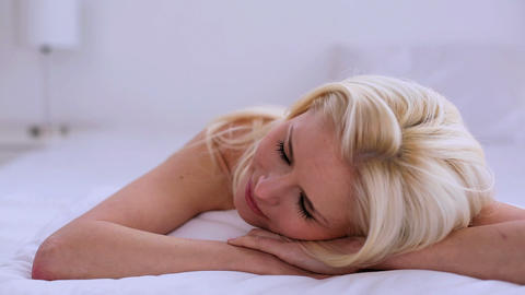 Beautiful blonde woman day dreaming while lying on Stock Video Footage