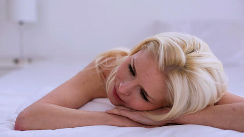 Beautiful blonde woman day dreaming while lying on Footage
