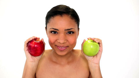 Beautiful young woman holding two apples smelling  Footage
