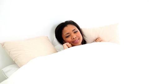 Beautiful dark haired woman lying in her bed wakin Footage