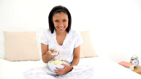 Amused young woman eating popcorn while watching t Footage