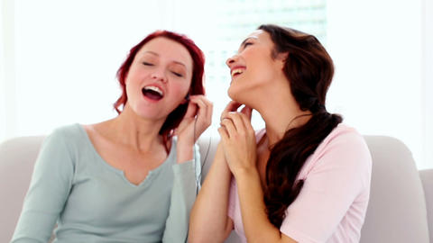 Two attractive women listening with headphones to  Footage