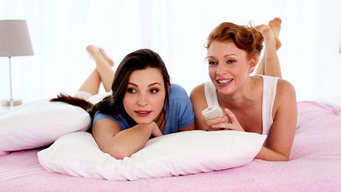 Talking Young Friends Lying On Pink Bed Watching T stock footage