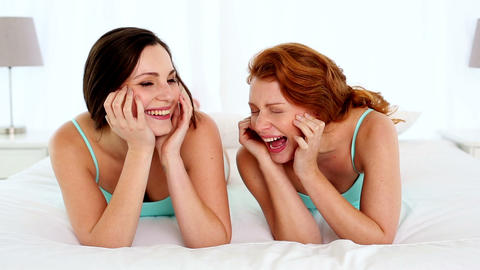 Amused laughing women lying on bed Footage