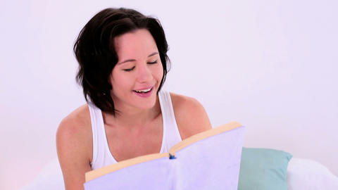Pretty woman reading a book while sitting on her b Footage