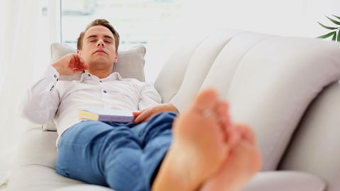 Attractive young man lying on couch while sleeping Footage