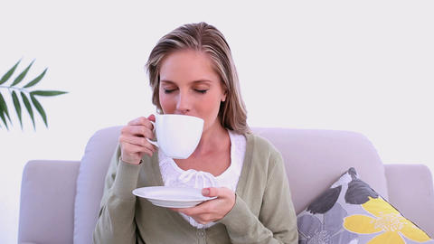 Content woman drinking from cup sitting on couch Footage