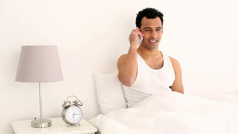 Happy handsome man sitting on bed phoning Footage