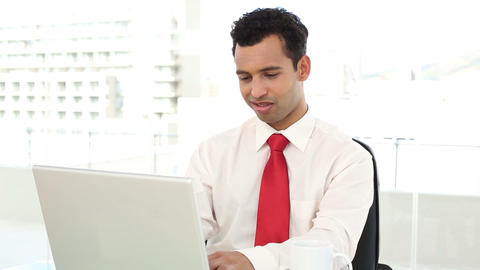 Smiling handsome businessman typing on laptop Footage