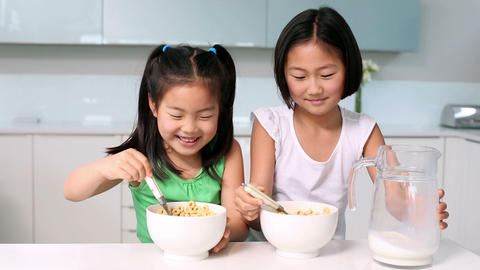 Two happy girls eating cereal Footage