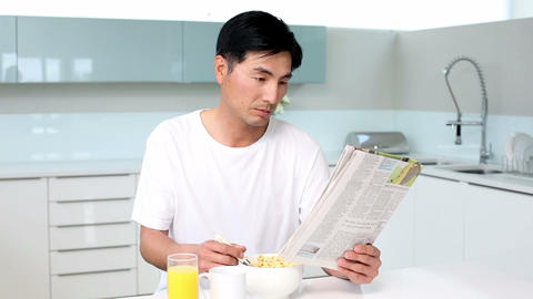 Attractive man eating cereal and reading magazine Footage