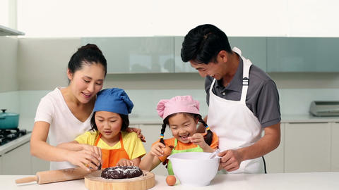 Smiling parents and cute daughters baking together Footage