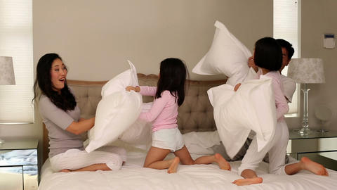 Silly family having a pillow fight on bed Footage