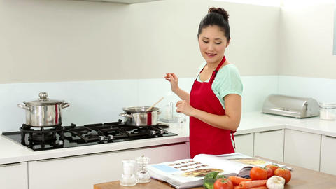 Smiling woman preparing dinner and consulting her  Footage