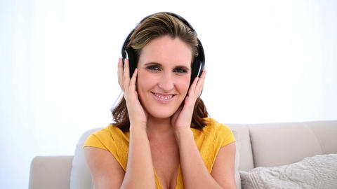 Smiling woman listening to music on the couch Footage