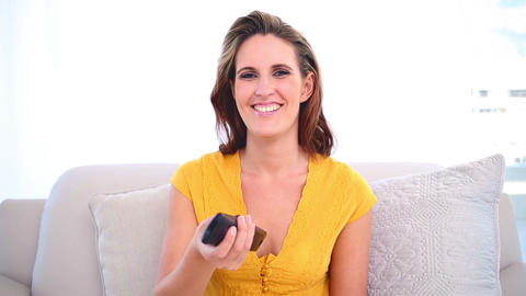 Smiling woman watching tv on the couch Footage