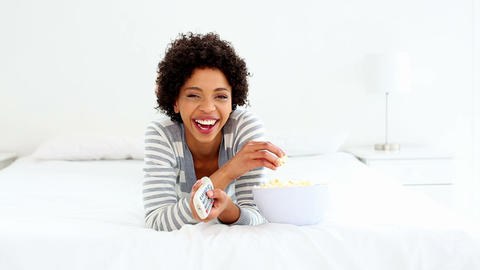 Cute laughing woman lying on bed watching tv Footage