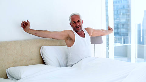 Smiling man yawning and stretching sitting on bed Footage
