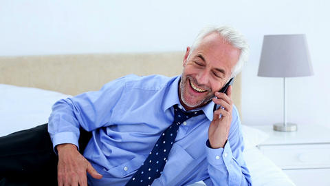 Businessman Answering A Phone Call Lying On His Be stock footage