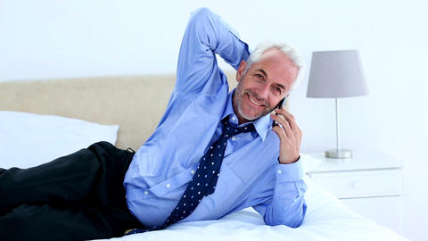 Businessman talking on the phone lying on his bed Footage