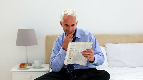Businessman sitting on bed reading newspaper in th Footage