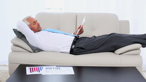 Businessman falling asleep holding paperwork on th Footage