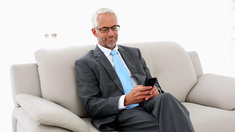 Businessman sending a text on the couch Footage