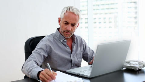 Casual businessman working on laptop at desk Footage