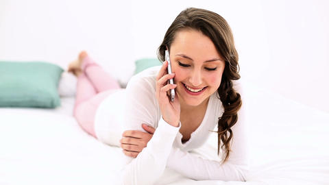 Smiling woman lying on bed chatting on the phone Footage